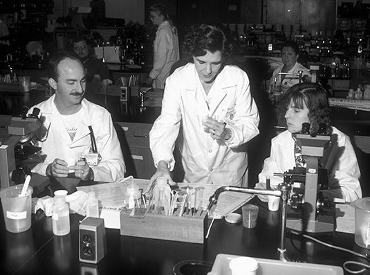 Black and white photo of Dr. Sharon Patton teaching students in the parasitology lab.
